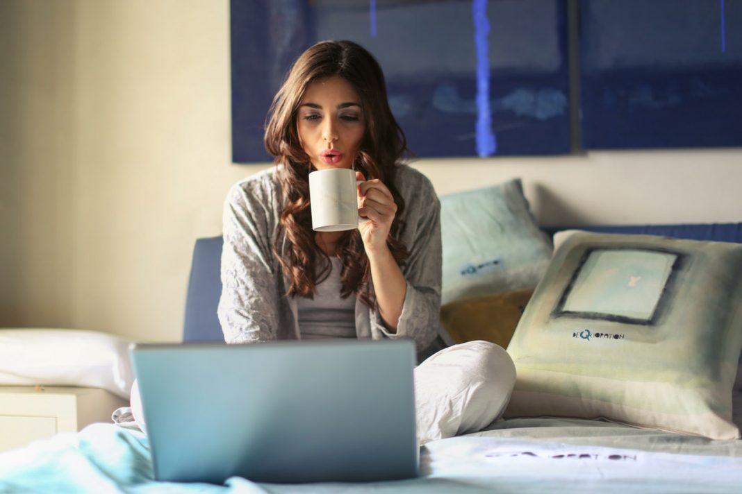 Una mujer está sentada sobre la cama mirando su ordenador y bebiendo de una taza