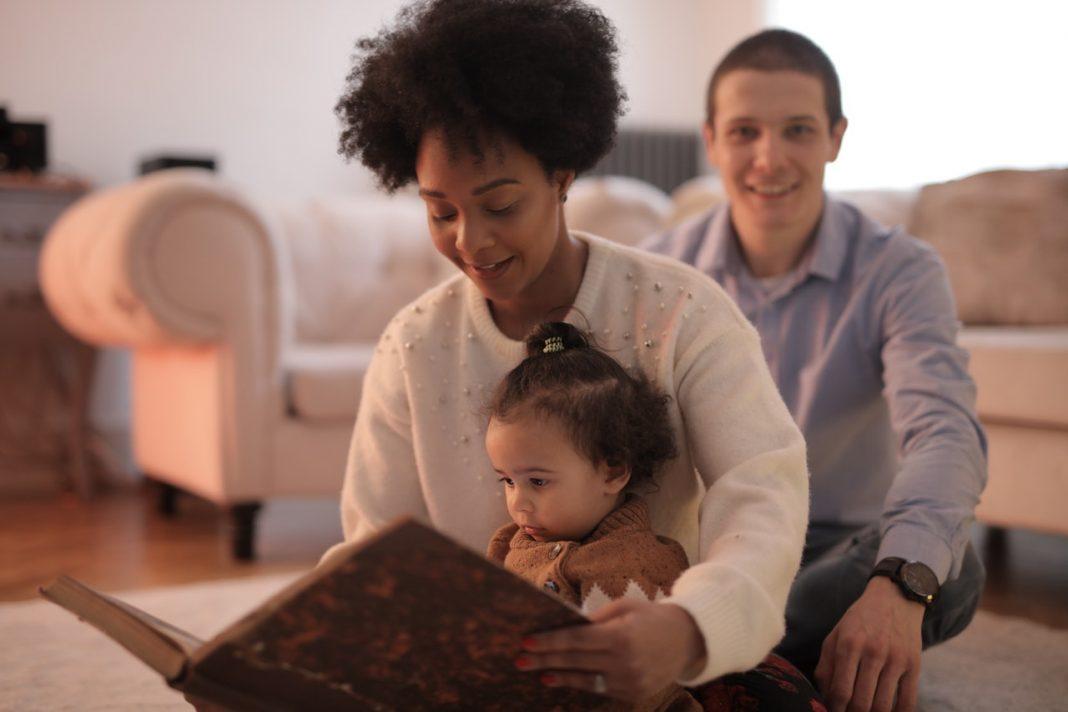 Historias coches: una mujer lee un cuento a una niña pequeña que está sentada sobre su regazo, con un hombre por detrás mirando. Parece una familia en el salón de su casa