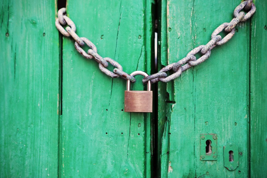 Alarma coche: imagen de una cadena bloqueada por un candado que cierra una puerta de madera de doble hoja.