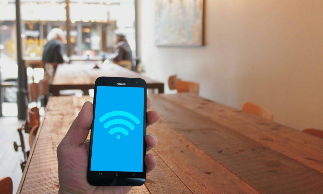 Imagen de un smartphone tratando de localizar Wifi en el interior de un bar