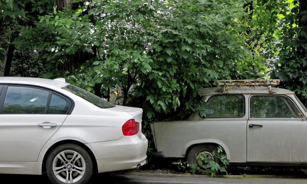 ciberataques coches: un coche moderno está aparcado sobre la acera, delante de otro viejo semi enterrado en hierbajos