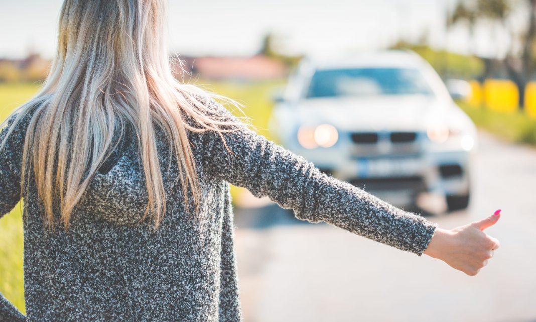 Mitos coche: una mujer espera a que la recoja un vehículo haciendo autostop