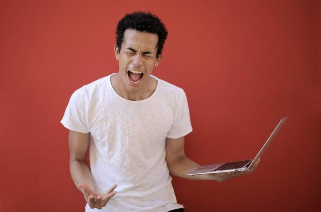 Seguridad webinar: un hombre sostiene un portátil en la mano mientras grita con gesto de desesperación