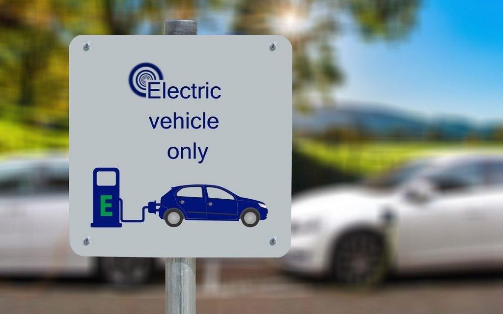 Imagen de un letrero delante de un punto de carga de coches eléctricos.