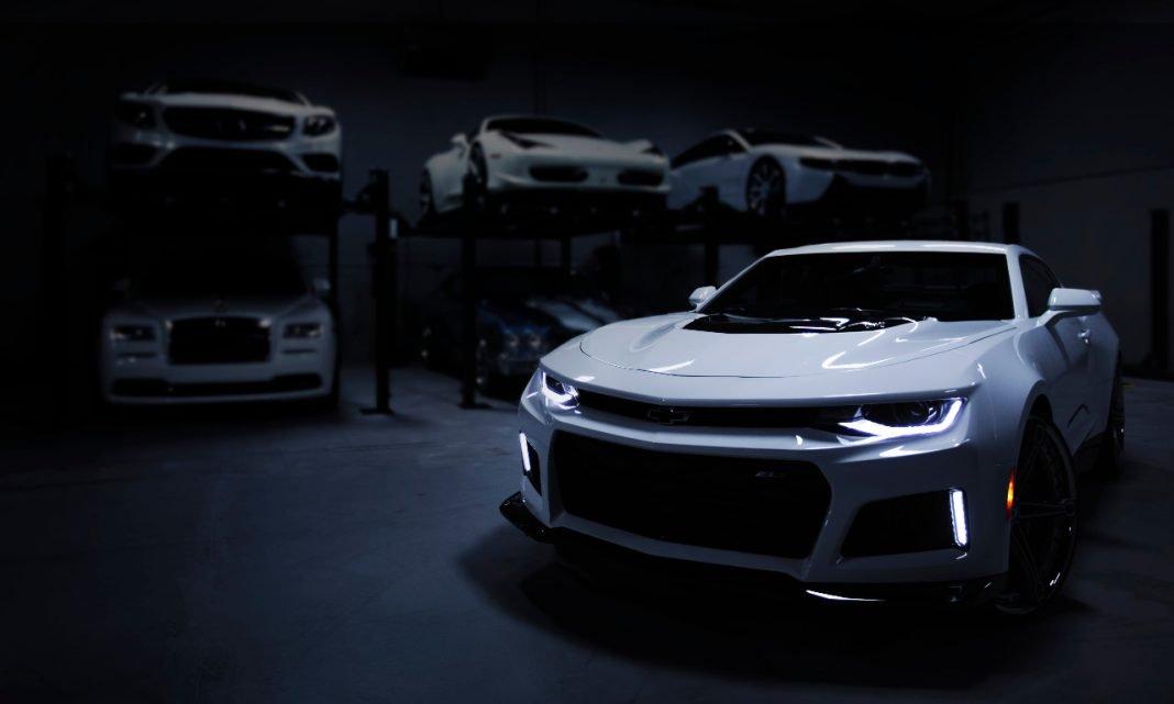 Llamadas a revisión deportivos: varios deportivos de color blanco aparcados en un garaje muy oscuro