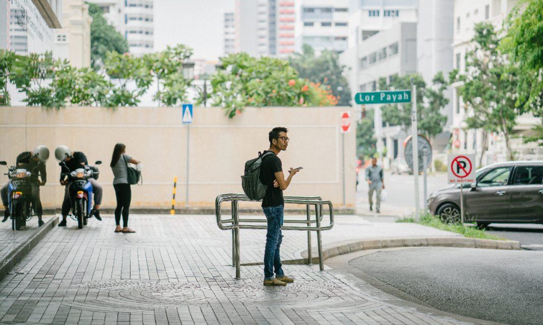 Reducir huella carbono: un hombre espera en el exterior de una estación de transporte público