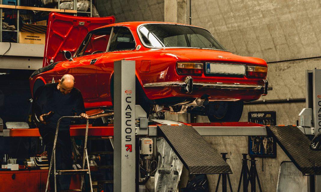 Llamadas a revisión coches: un coche clásico está subido a un elevador en un taller