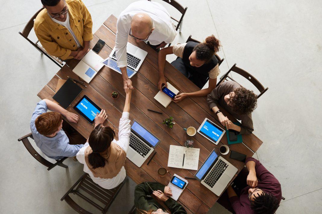 Seguridad dispositivos conectados: imagen cenital de un grupo de personas sentadas en torno a una mesa, todas ellas usando un ordenador o un teléfono móvil