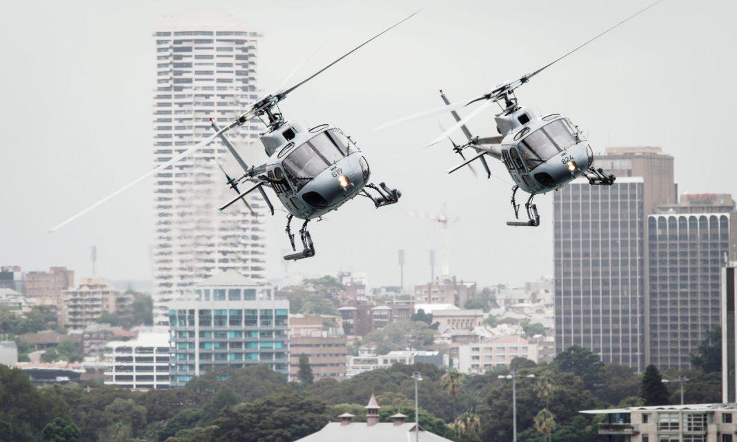 Transporte aéreo: dos helicópteros sobrevuelan a baja altura una ciudad de rascacielos