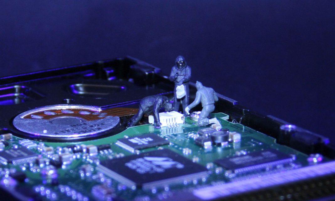 Robo de datos: imagen de unas figuritas de ladrones que están actuando sobre un microchip