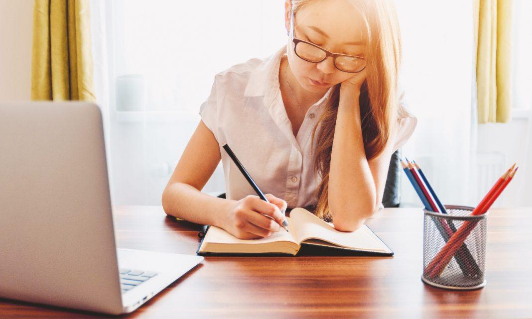 Estudiar ciberseguridad: una chica aparece estudiando en un despacho delante de un ordenador y un libro