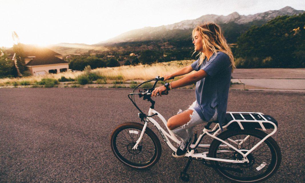 Generación Z: imagen de una mujer joven desplazándose por una carretera en bicicleta de ciudad