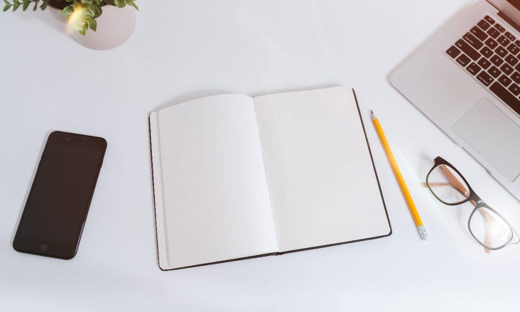 Imagen de una mesa con un cuaderno, ordenador y lápiz sobre ella