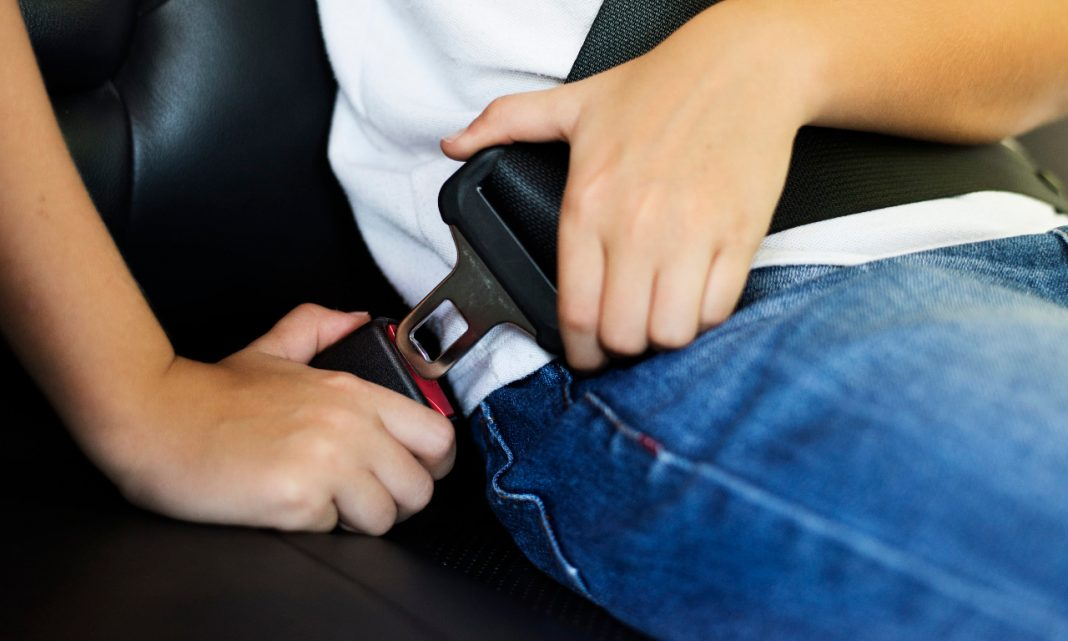 Mes de la ciberseguridad: primer plano de una persona abrochándose el cinturón de ciberseguridad en un coche