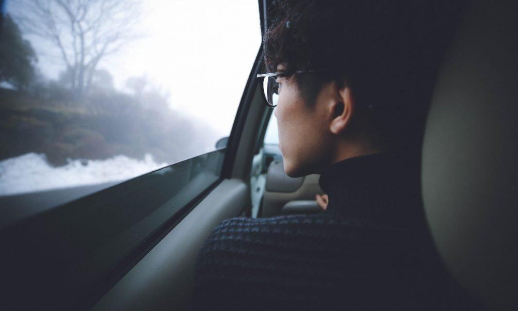Imagen de un hombre con rasgos orientales sentado en el asiento del conductor de un coche y mirando por la ventanilla con gesto serio