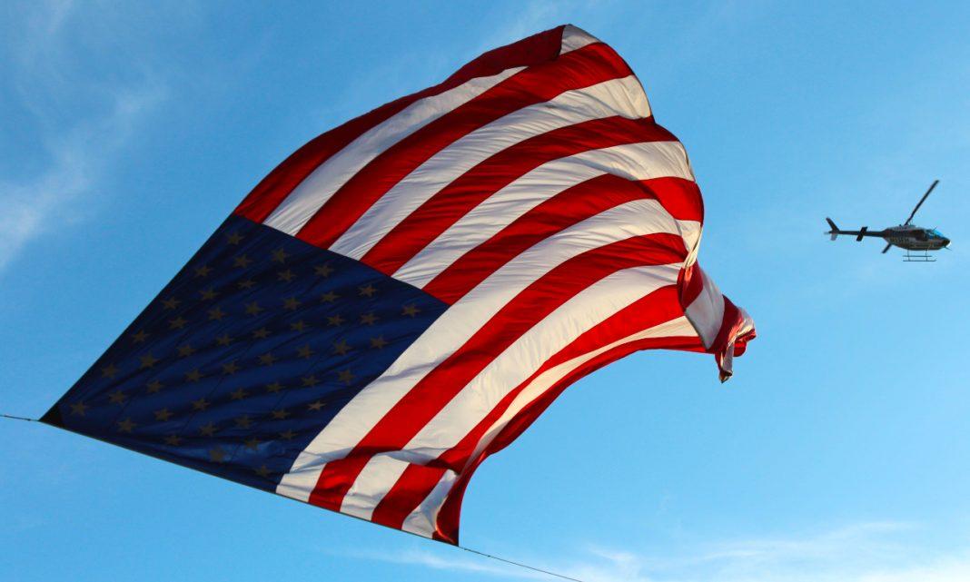 Imagen de una bandera estadounidense ondeando al viento mientras vuela un helicóptero militar