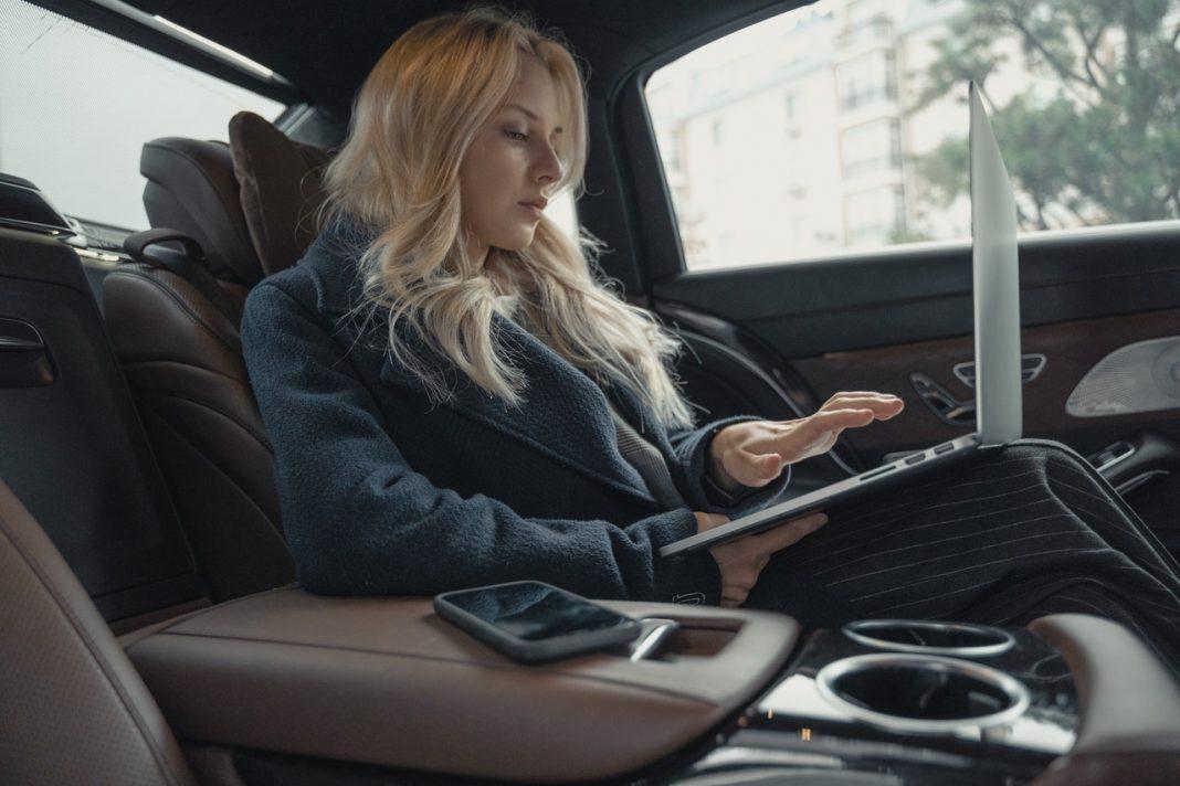Imagen de una joven sentada en el asiento trasero de un coche de lujo mientras maneja un ordenador portátil