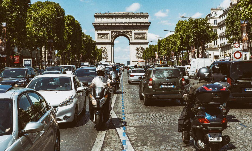 Imagen de una avenida de París llena de tráfico, con el Arco del Triunfo de fondo