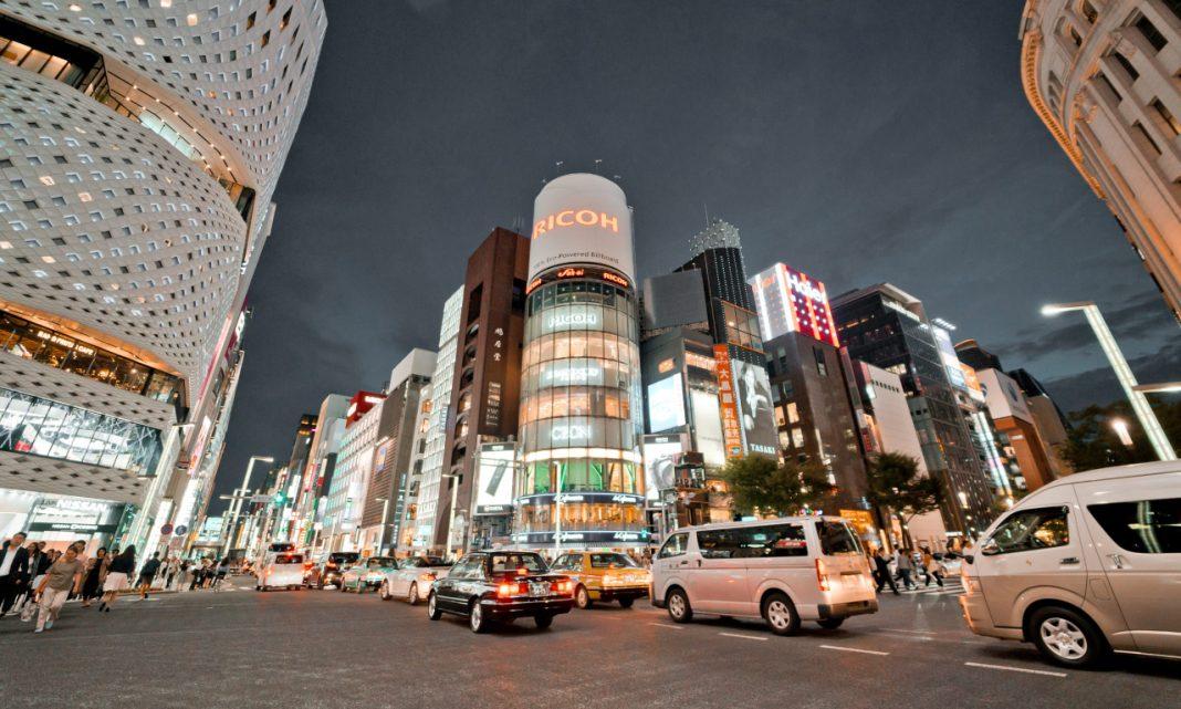 Imagen de una calle de una ciudad japonesa llena de tráfico y con carteles de neón en los edificios