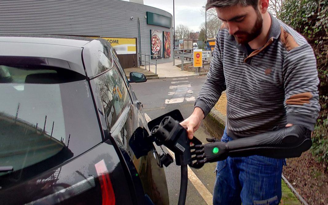 Imagen de un conductor discapacitado recargando un coche eléctrico