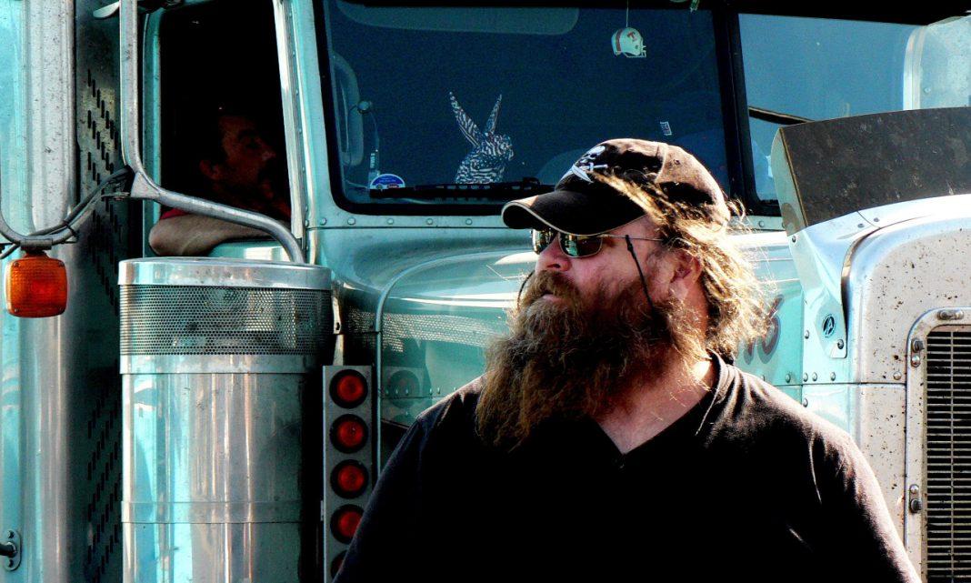 Imagen de un camionero barbudo delante de un camión de estilo americano