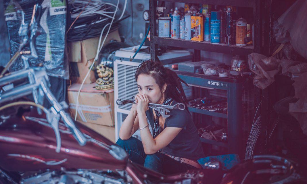 Imagen de una chica sentada en el suelo de un taller de motos, rodeada de herramientas.