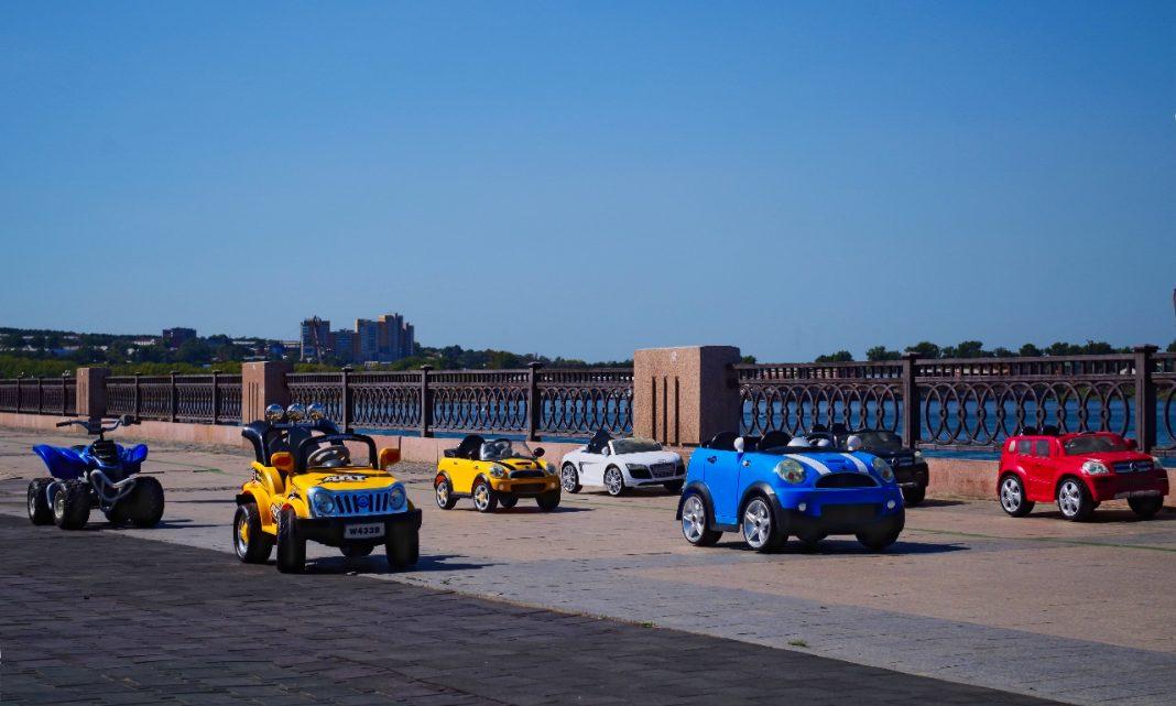 Imagen de varios coches para niños aparcados sobre la acera de un paseo marítimo