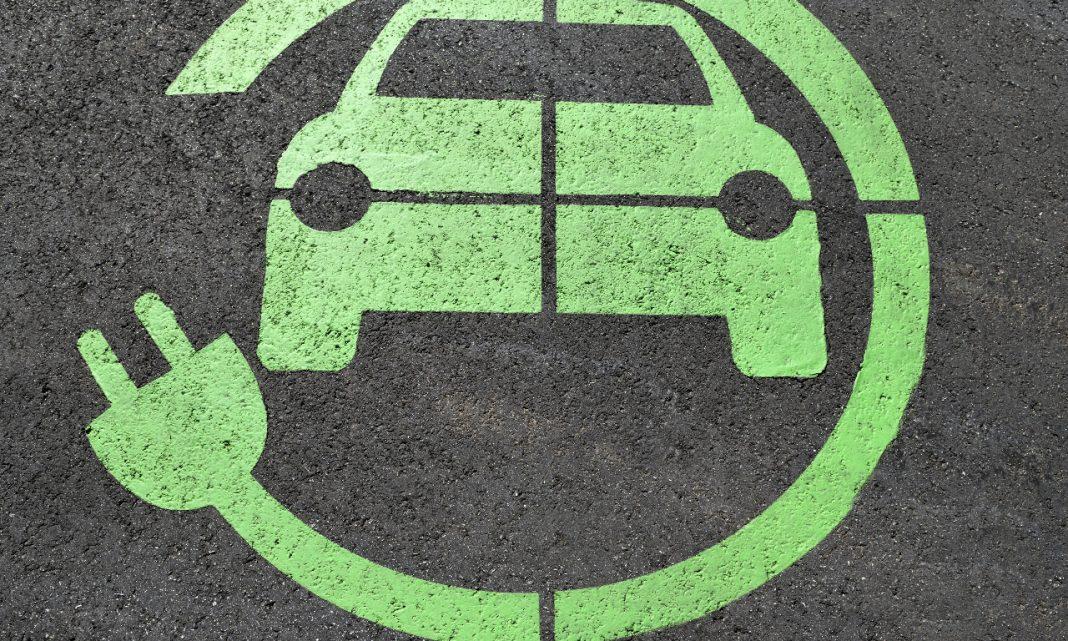 Imagen del suelo de una plaza de parking con el símbolo de un coche eléctrico dibujado