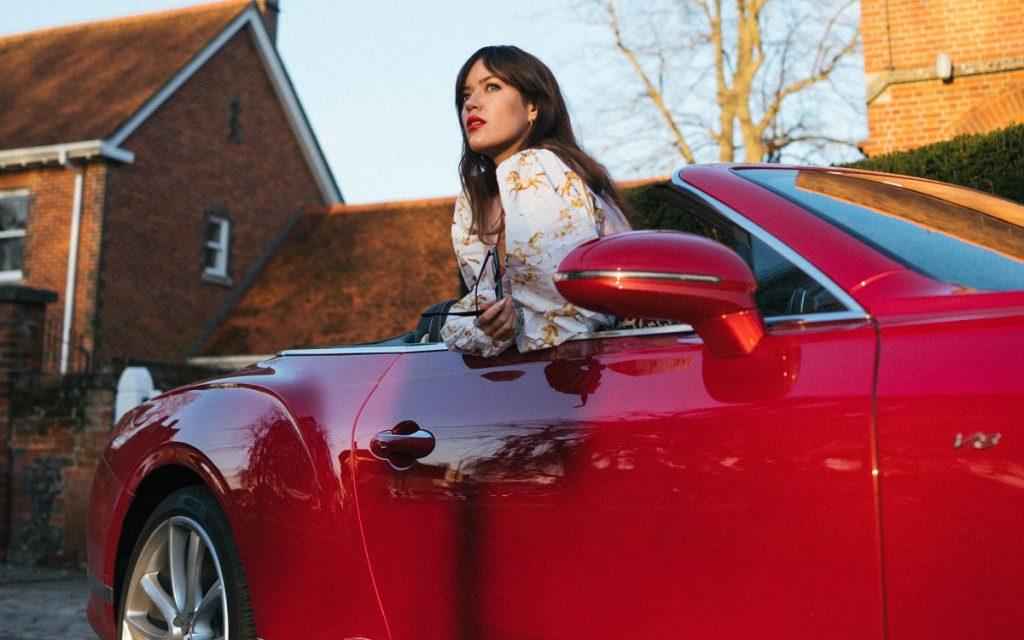 Imagen de la poetisa Charly Cox con un Bentley Continental GT Cabrio