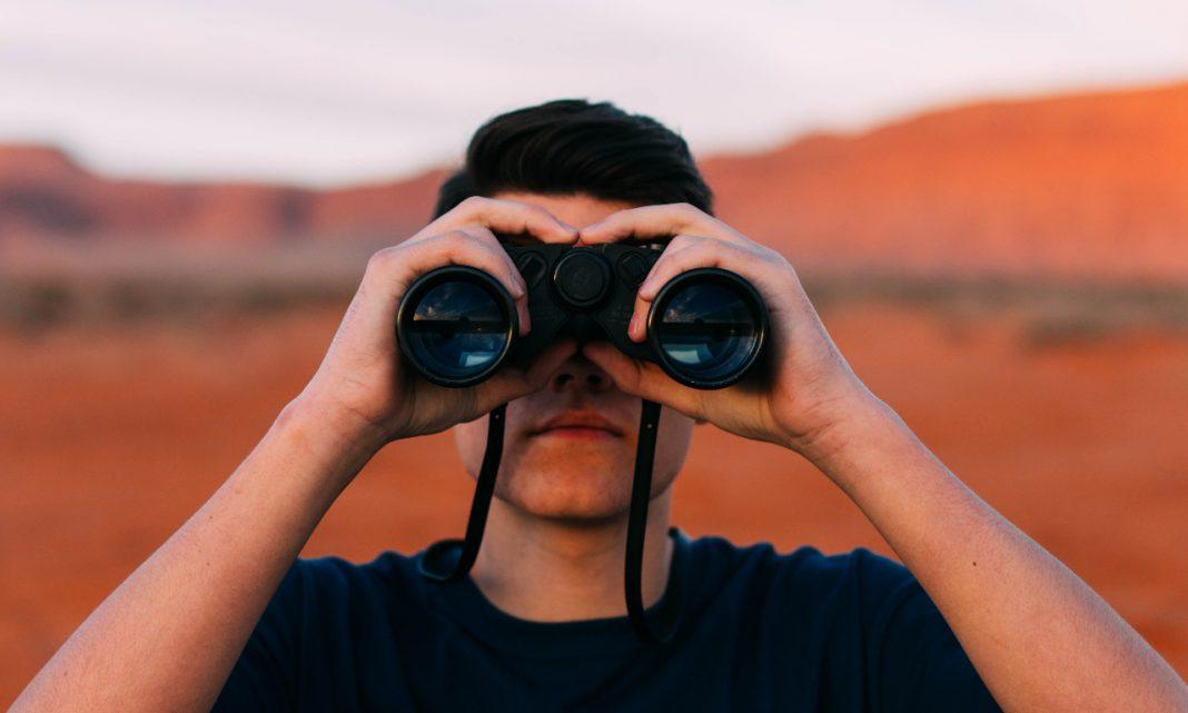 Imagen de un hombre joven, en mitad de un desierto, mirando al horizonte a través de unos prismáticos negros.