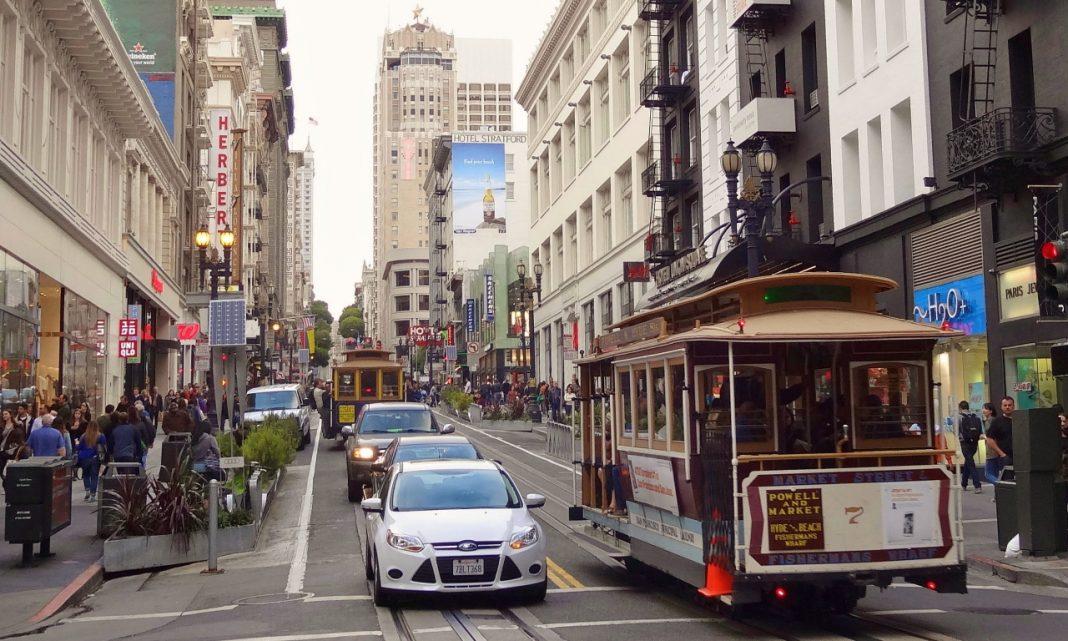 Imagen de una calle de San Francisco, con varios vehículos y un tranvía circulando por ella.