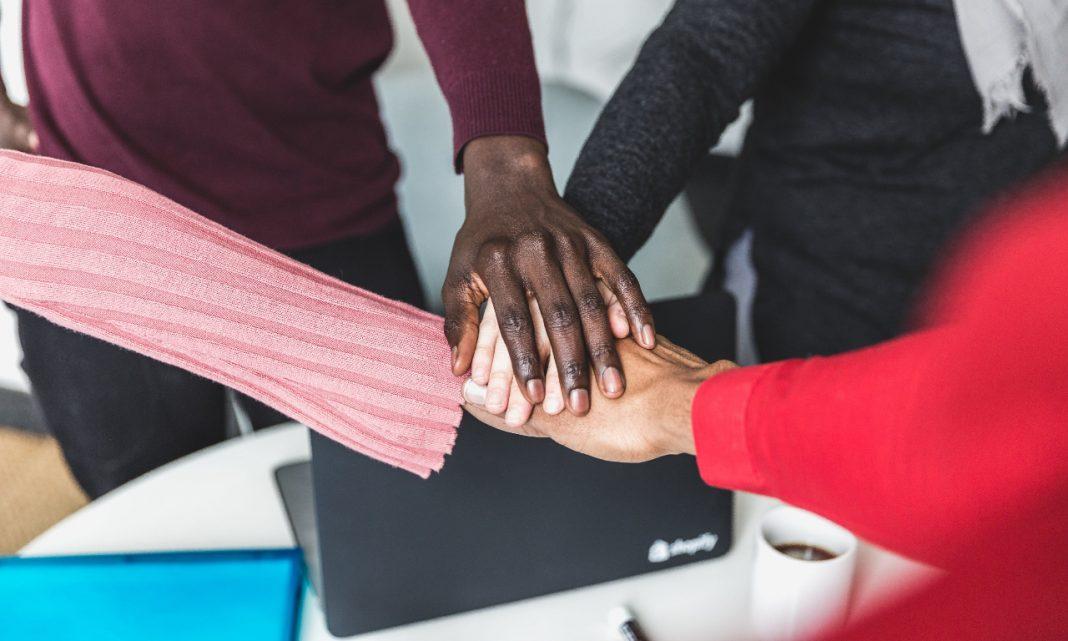 Imagen de unas personas uniendo sus manos todos a la vez, unas manos sobre las otras