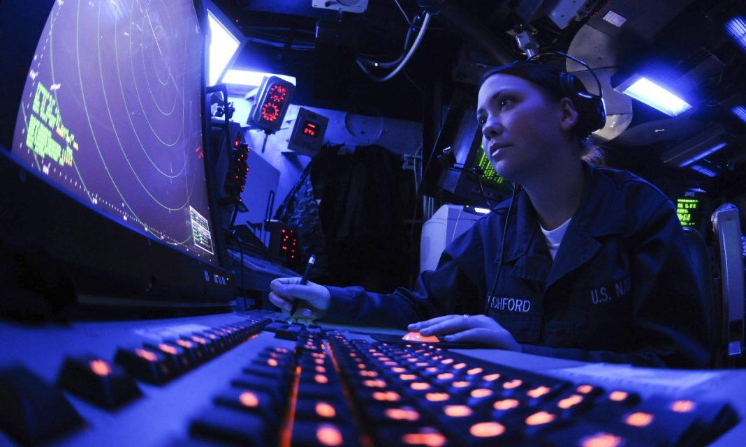 Imagen de una militar dentro de una sala oscura trabajando con un ordenador