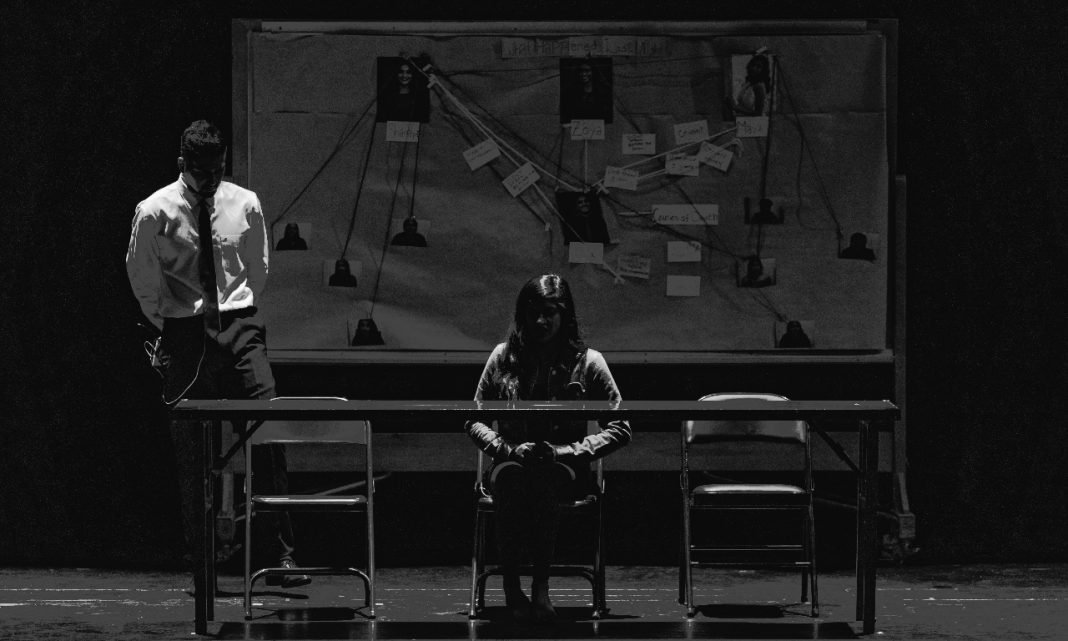 Imagen de una sala de interrogatorios de la policia, muy oscura, con una mujer sentada en la mesa y un hombre en camisa de pie junto a ella