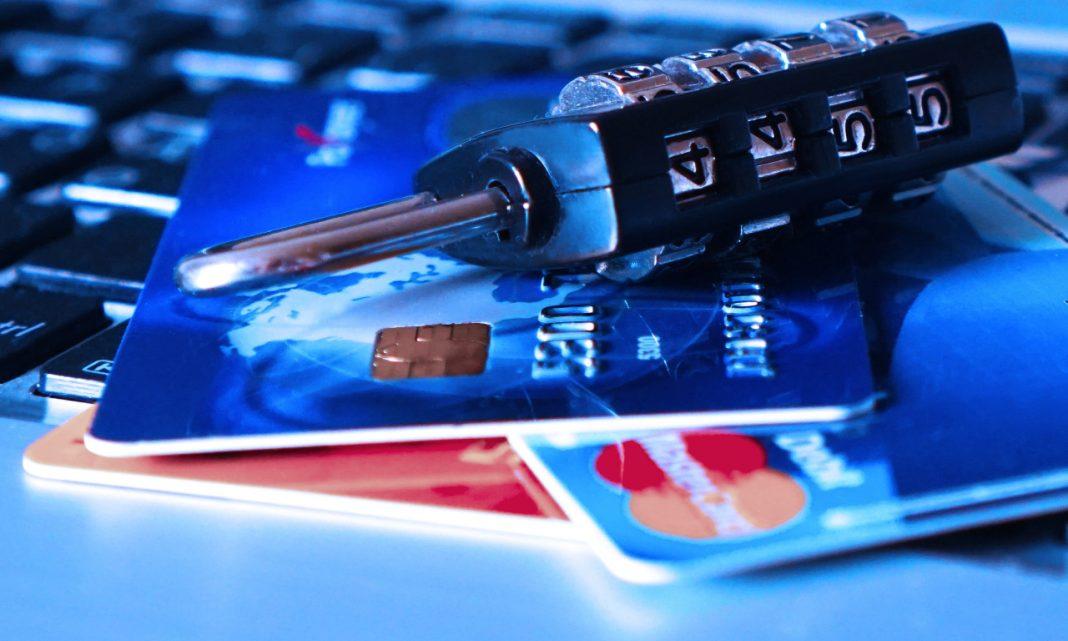 Imagen de un candado depositado sobre unas tarjetas de crédito y un ordenador