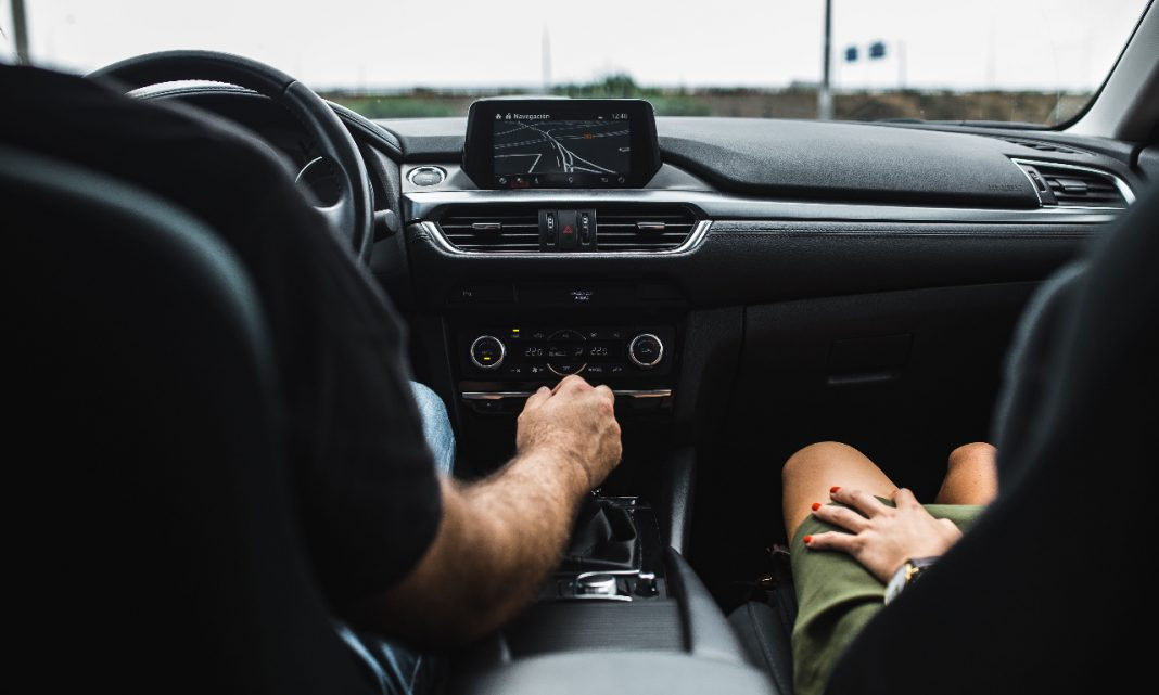 Imagen de las plazas delanteras de un coche con dos personas a las que no se les ve la cara sentadas en ellas