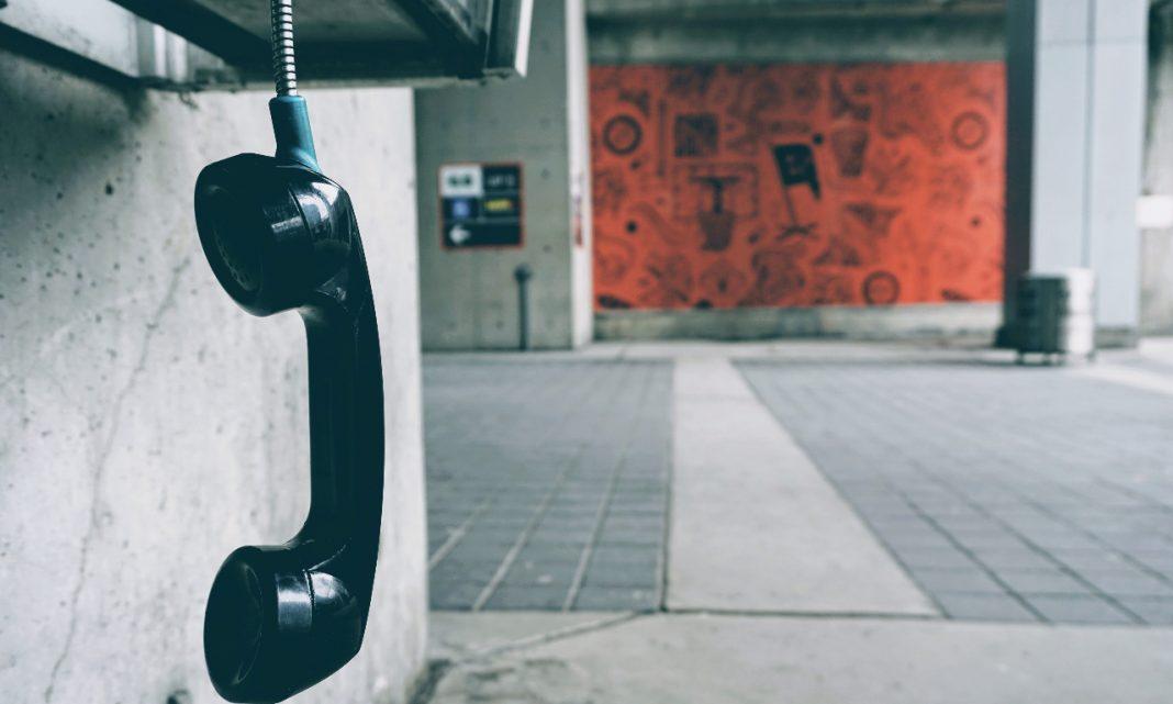 Imagen de un teléfono público descolgado y colgando hacia el suelo