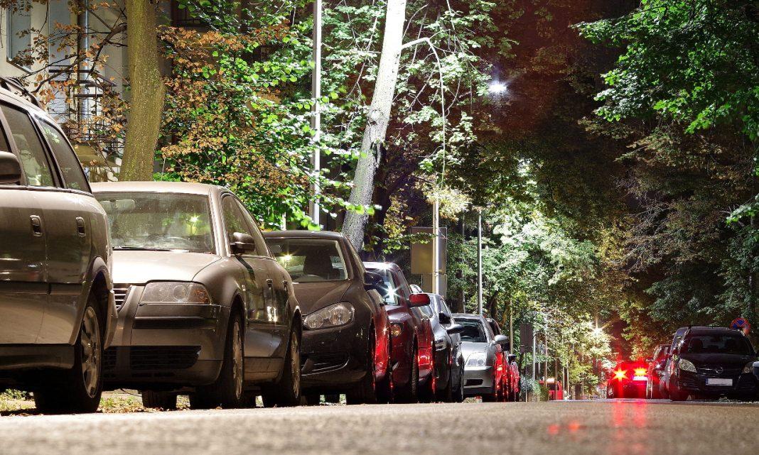 Imagen de una calle por la noche, repleta de coches aparcados a ambos lados