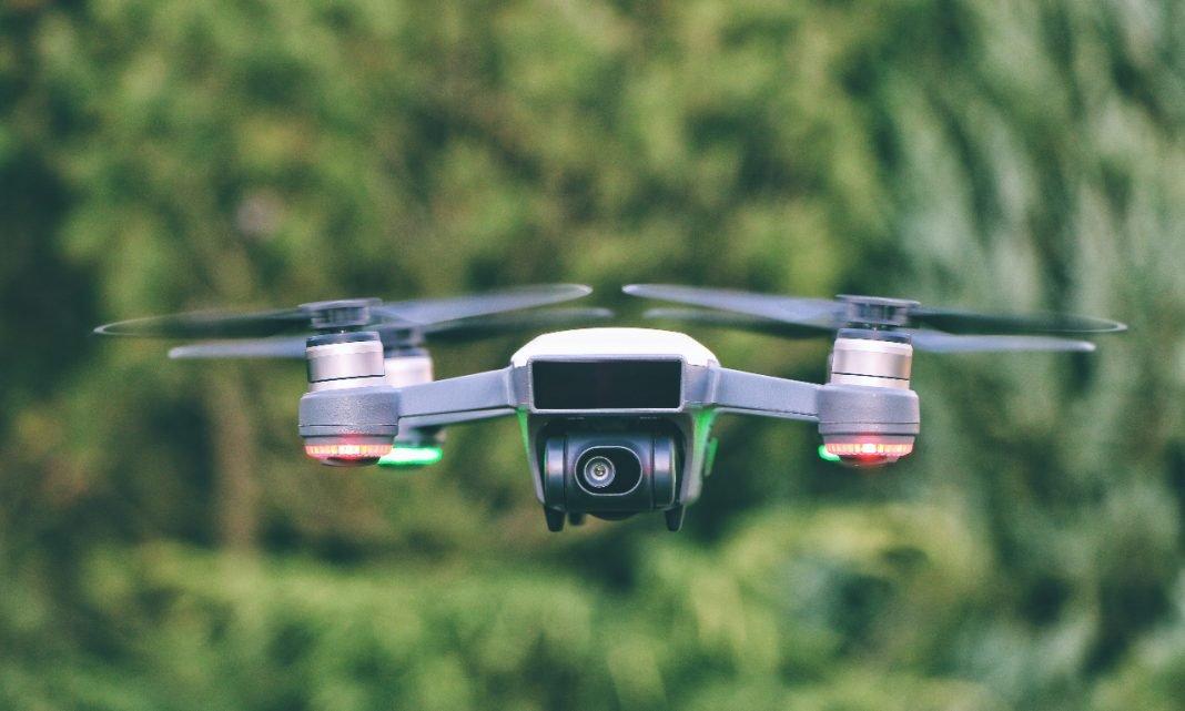 Imagen de un dron volando con unos árboles de fondo