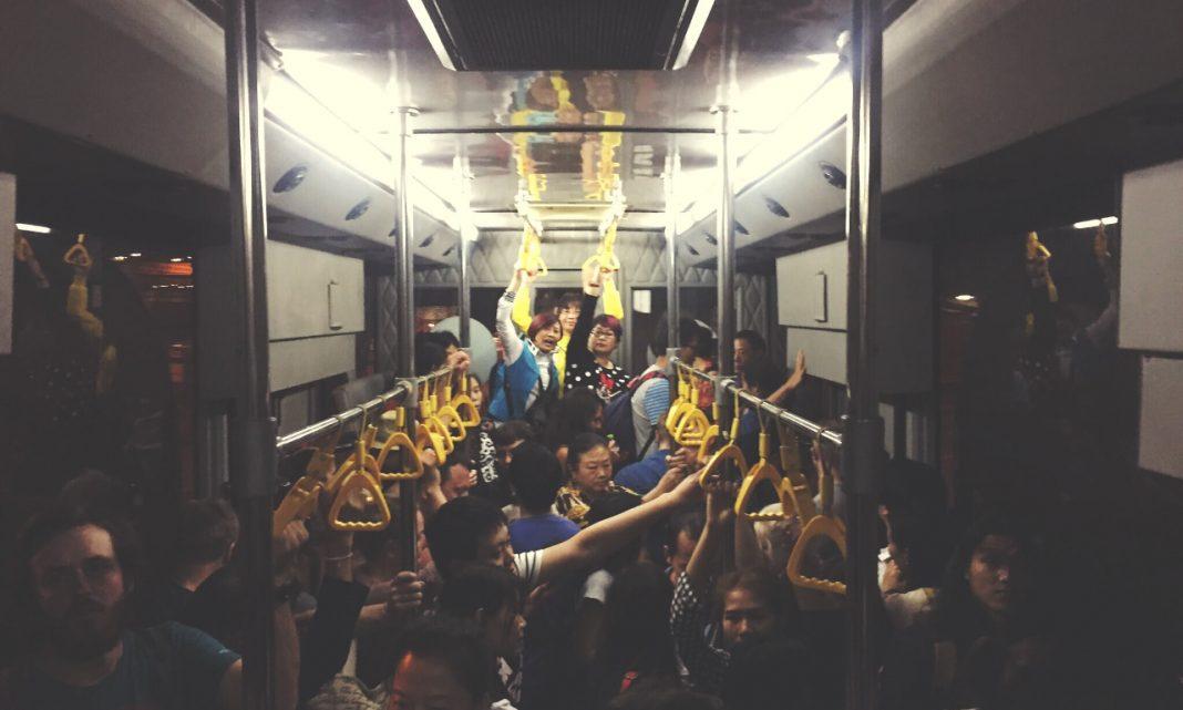 Imagen de muchas personas de raza oriental hacinadas en el interior de un vagón de metro