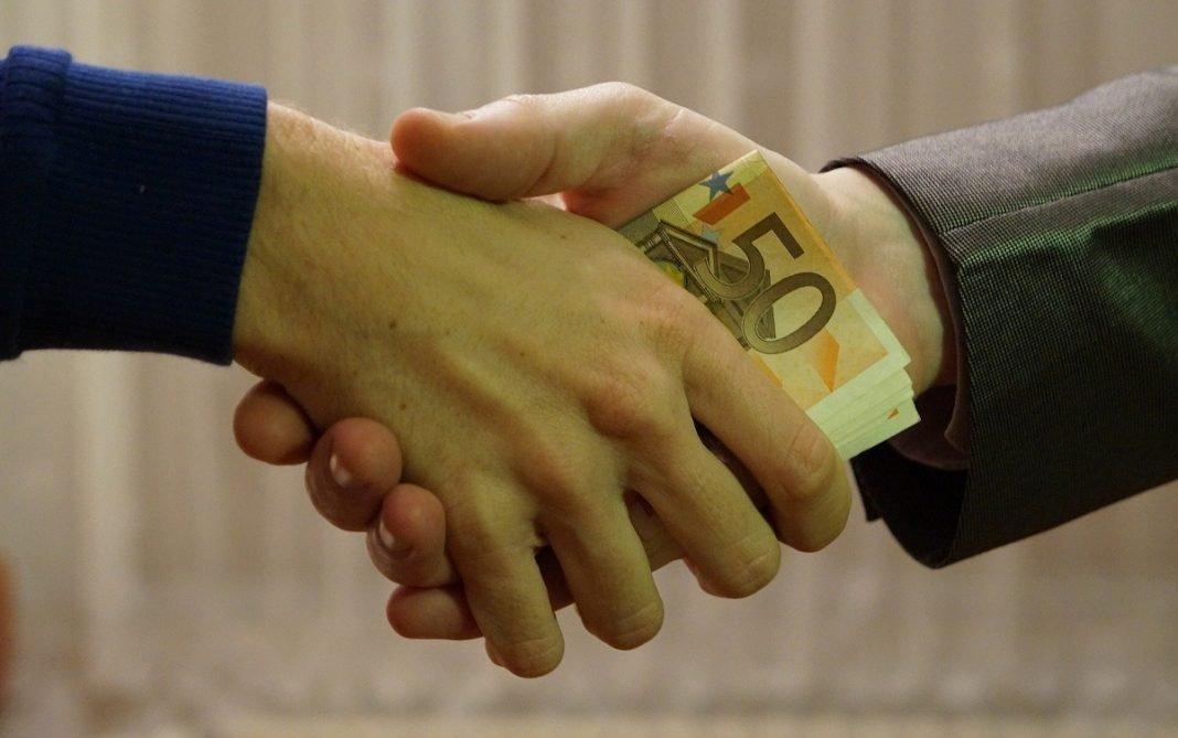 Imagen de manos cambiando dinero