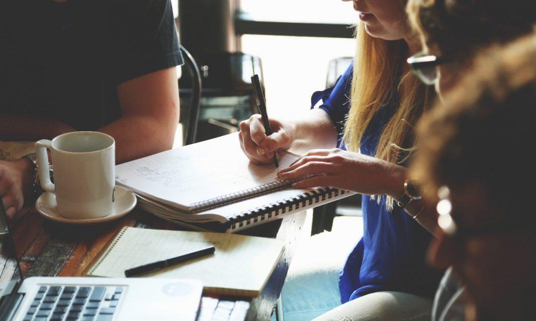 Imagen de un equipo de personas trabajando en una cafetería delante de un cuaderno y varios papeles