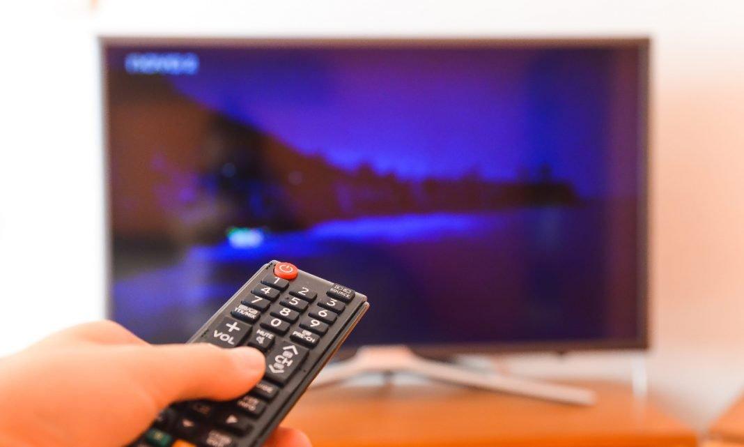 Imagen de una persona encendiendo la TV con el mando a distancia