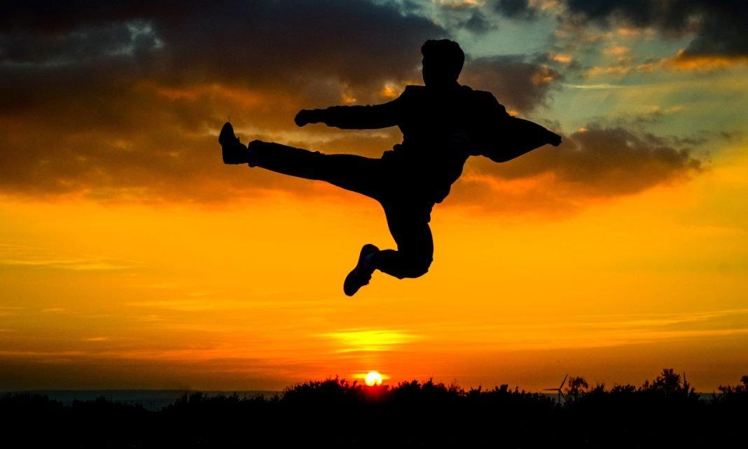Imagen de una persona dando una patada de kárate con salto en contraste con una puesta de Sol